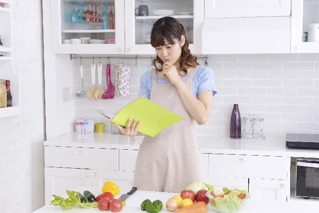 美肌になるレシピを見ながら何を作ろうか悩む女性